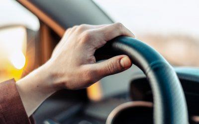 Closeup guy hand on car steering wheel.